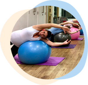 Pregnant ladies exercising using gym balls in studio